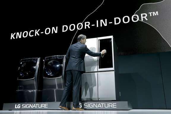 FILE - In this Tuesday, Jan. 5, 2016, file photo, David VanderWaal, vice president of marketing for LG Electronics USA, knocks on the door of a new LG Signature refrigerator during a news conference preview for CES International, in Las Vegas. LG Electronics lets you peek through an opaque glass window on one of the double-doors that lights up from the inside with a tap, saving electricity and maybe keeping you from making a poor decision about a late night snack. (AP Photo/Gregory Bull, File)