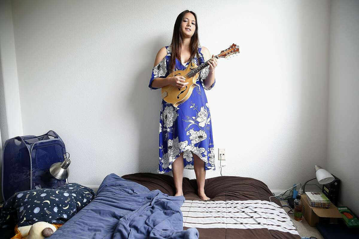 AJ Lee, 19 year old singer, mandolinist, fiddler and guitarist from Santa Cruz plays music in her room on Thursday, June 8, 2017, in Santa Cruz, Calif.