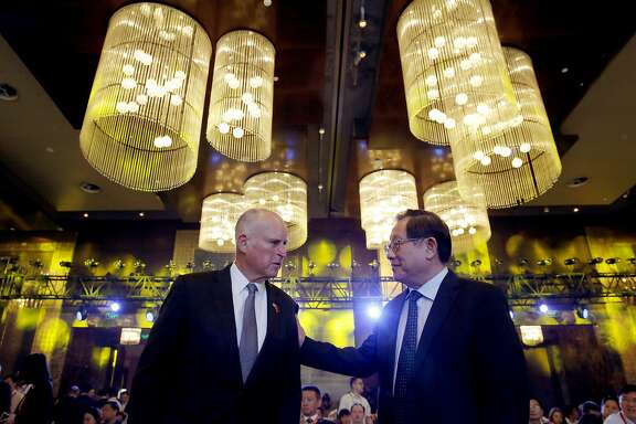 California Gov. Jerry Brown, left, chats with China's Science and Technology Minister Wan Gang as they attend the Clean Energy Ministerial International Forum on Electric Vehicle Pilot Cities and Industrial Development, at a hotel in Beijing, Tuesday, June 6, 2017. (AP Photo/Andy Wong)