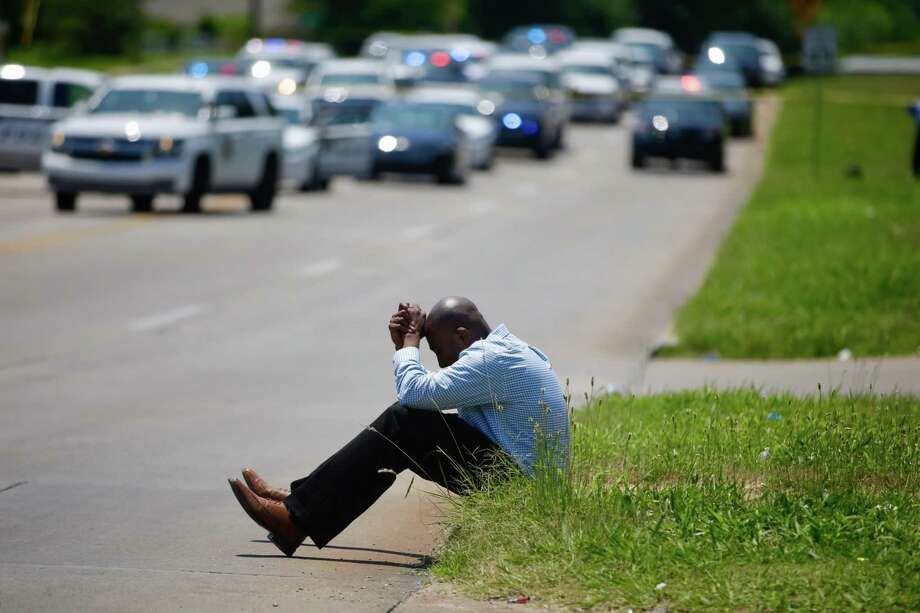Police Chaplain Andru Morgan prays at the scene of an officer involved shooting, Friday, June 9, 2017 in Tulsa, Okla. Law officers in Tulsa fatally shot a man while trying to pick him up for a mental health issue, triggering a street protest and a corresponding show of force by police in riot gear. (Mike Simons/Tulsa World via AP) Photo: Mike Simons, MBI / CORY YOUNG/Tulsa World