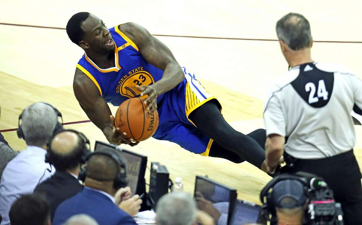 Golden State Warriors' Draymond Green tries to save a ball from going out of bounds in 4th quarter of Cleveland Cavaliers' 137-116 win in Game 4 of NBA Finals at Quicken Loans Arena in Cleveland, Ohio, on Friday, June 9, 2017.