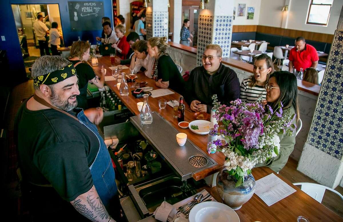 Chef Telmo Faria talks with customers at the bar at Uma Casa.