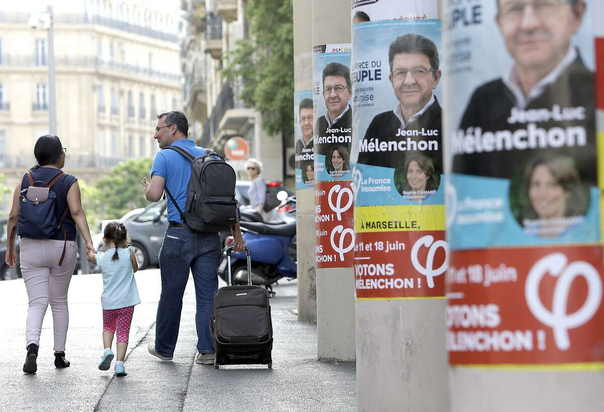 People walk past near posters of Jean-Luc Melenchon, a former hard-left candidate in the first round of the presidential election, candidate for the upcoming legislative elections, at the Belsunce district, in Marseille, southern France, Friday, June 9, 2017. One month after President Emmanuel Macron�s arrival in power, French voters must now choose lawmakers in parliamentary elections starting Sunday that may dramatically reshape the political landscape. (AP Photo/Claude Paris)