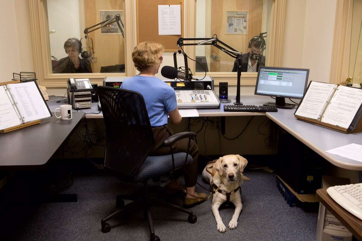 CRIS volunteer and listener, Diane Duhaime, produces a live afternoon news program each week with CRIS volunteer readers Sue Carey, left, and Ruth Bowman. Pictured with Duhaime is her guide dog Iroc.