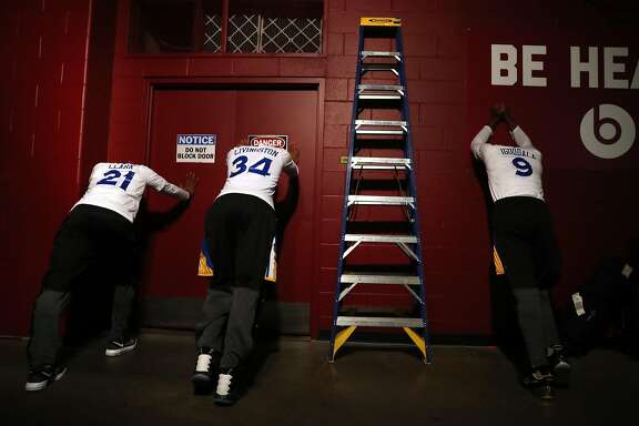 Golden State Warriors' Ian Clark, Shaun Livingston and Andre Iguodala stretch before Cleveland Cavaliers' 137-116 win in Game 4 of NBA Finals at Quicken Loans Arena in Cleveland, Ohio, on Friday, June 9, 2017.