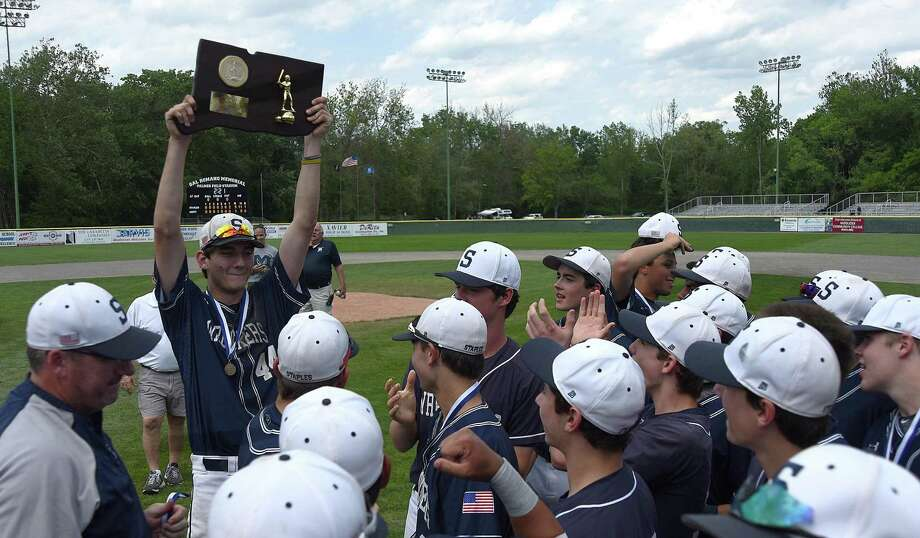 Staples captain Mike Fanning, top left, hoists the Class LL state championship trophy above his head as he and his teammates celebrate Saturday's 5-1 win over top-seeded Amity at Palmer Field in Middletown. Photo: John Nash / Hearst Connecticut Media / Norwalk Hour