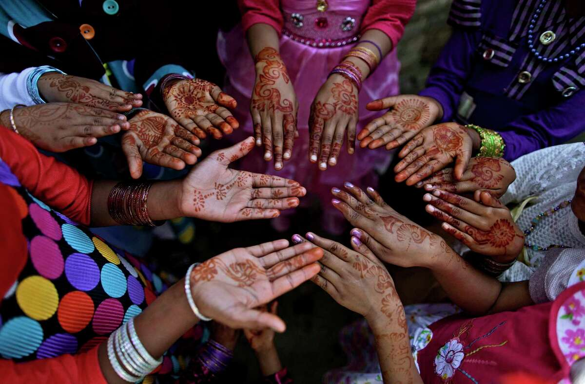 Pakistani Christian girls, display their hands decorated with Bangles and painted with Henna paste as they celebrate Easter holiday following a mass at in a Christian neighborhood in Islamabad, Pakistan, Sunday, March 31, 2013. Pakistan's Christians, are celebrating Easter along with other Christian nations. (AP Photo/Muhammed Muheisen)
