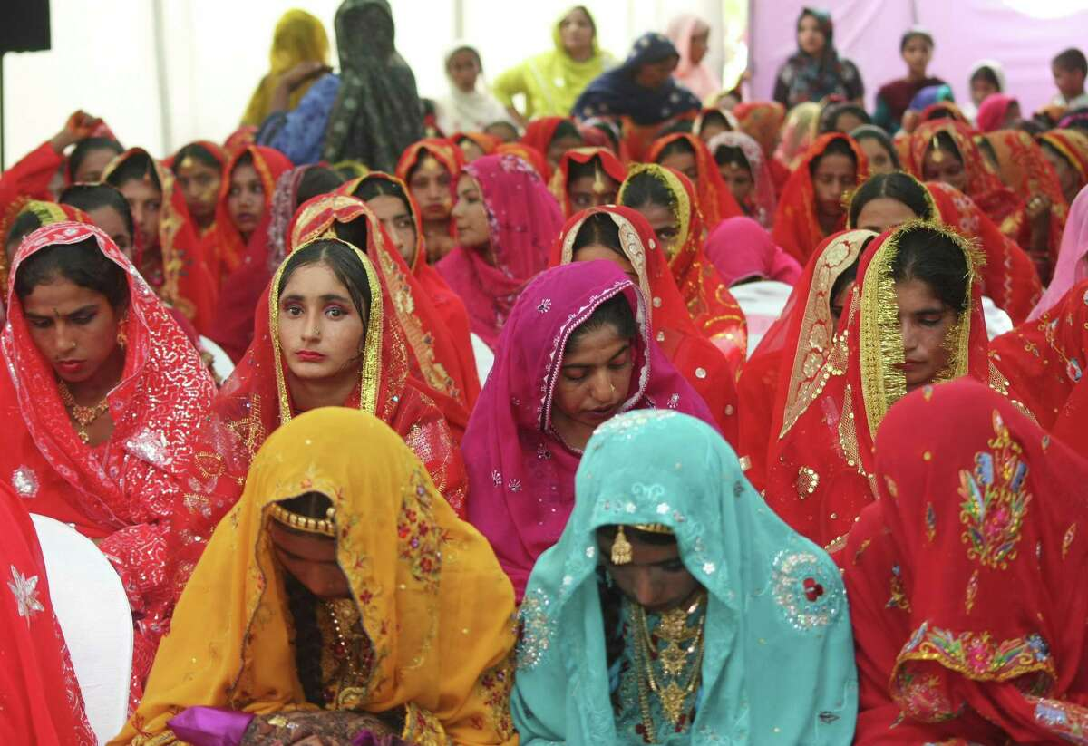 Pakistani government arranges a mass marriage ceremony for poor people which is attended by 150 brides and grooms in Karachi, Pakistan on Friday, June 5, 2009. (AP Photo/Fareed Khan)