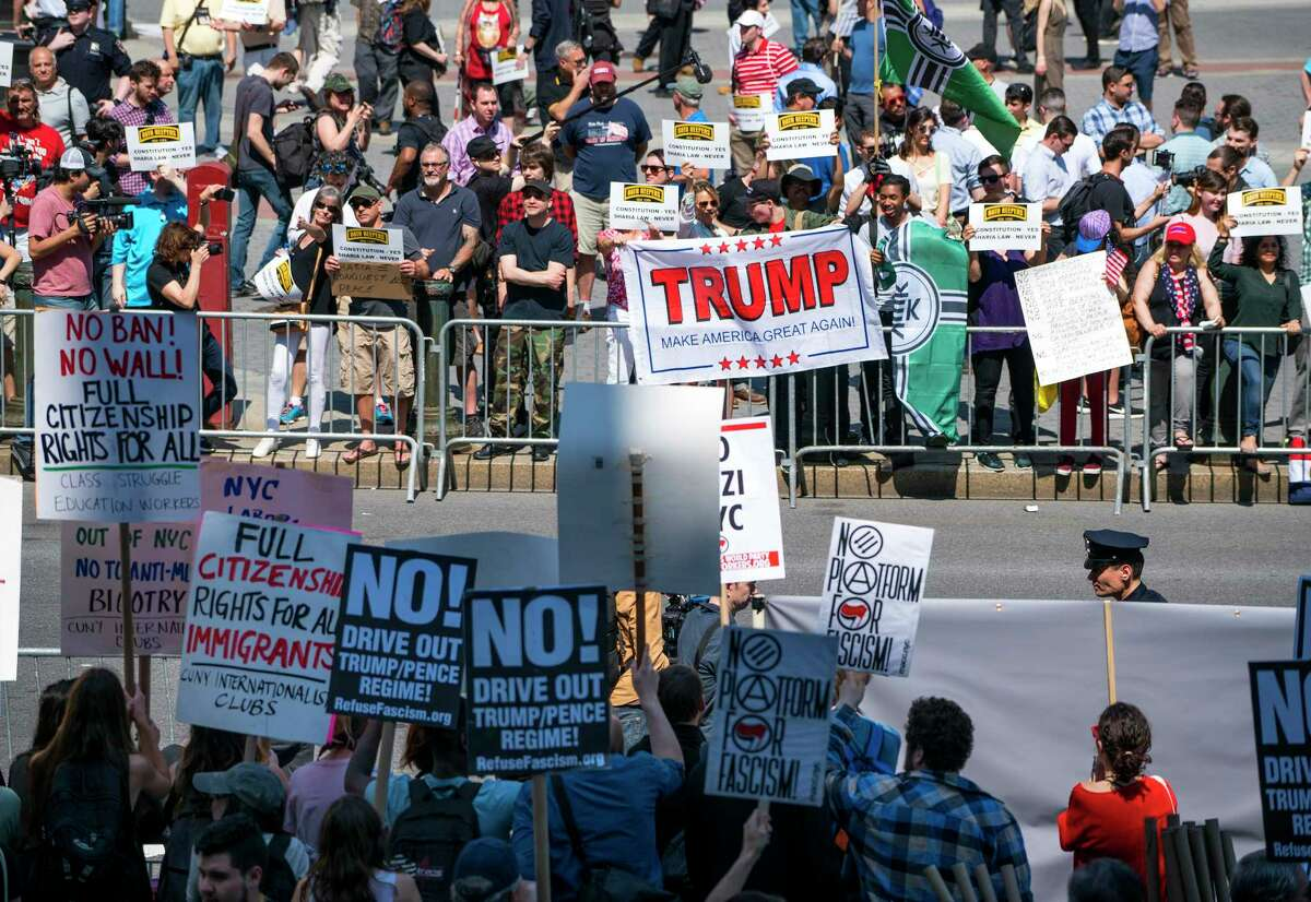 Demonstrators against Islamic law (background) gather in New York Saturday, June 10, 2017, as counter demonstrators line up across Centre St., foreground. Marches against Islamic law were planned Saturday in more than two dozen cities across the United States, but scholars and others say the protesters are stoking unfounded fears and promoting a distorted and prejudiced view of the religion. (AP Photo/Craig Ruttle)