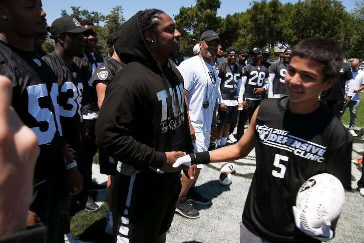 Oakland Raiders running back Marshawn Lynch congratulates Castlemont sophomore Carlos Reales (5)  during a defensive drills clinic for area prep football players,  Saturday, June 10, 2017, at the Raiders' headquarters in Alameda, Calif.