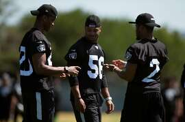 Oakland Raiders rookies Obi Melifonwu, from left, Xavier Woodson-Luster and Gareon Conley compare notes during a defensive skills clinic for area prep football players,  Saturday, June 10, 2017, at the Raiders' headquarters in Alameda, Calif.