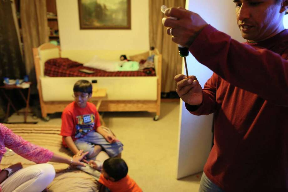Fahd Afeef prepares a dose of  Cannabidiol (CBD) for his son Ibrahim Afeef , who has greatly suffered from epileptic seizures starting around the age of five. The use of Cannabidiol (CBD), a cannabis compound, has almost eliminated his epileptic seizures and has improved the families quality of life in Colorado Springs, Colo., Tuesday, April 7, 2015. The family moved from San Antonio to have access to CBD for their son. (Photo by Barry Gutierrez) Photo: Barry Gutierrez, Owner / Barry Gutierrez Photography / Barry Gutierrez Photography  Barry Gutierrez  303-549-6742 barry@barrygutierrez.com  3817 Clay Street Denver, CO, 80211