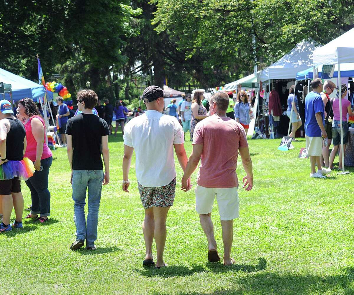 Norwalk residents Steven Bedoya, left, and Greg Ulrich held hands as they walked through the Triangle Community Center's annual Pride in the Park celebration at Mathews Park in Norwalk on Saturday.