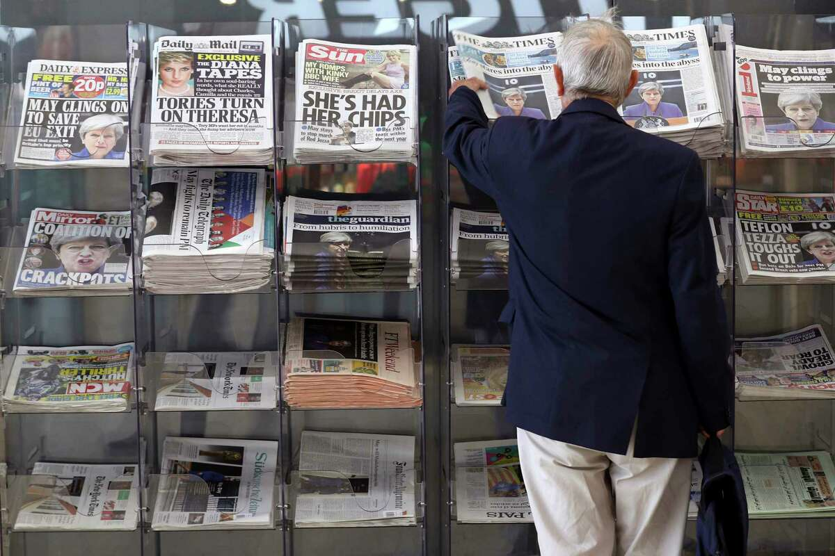 A man picks up a newspaper reporting the development following Britain's general election at a shop in Westminster in London, Saturday June 10, 2017. Beleaguered British Prime Minister Theresa May is appointing new members of her government after several of them lost their seats in Parliament in this week's general election that proved disastrous for her Conservative Party.(AP Photo/Tim Ireland)