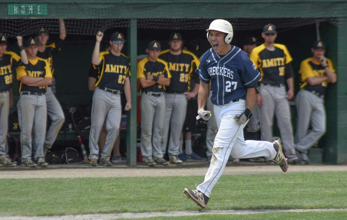 Staples sophomore Chad Knight reacts as he runs down the third baseline toward home plate after hitting the go-ahead two-run home run in the fifth inning of Saturday's Class LL championship game against Amity.