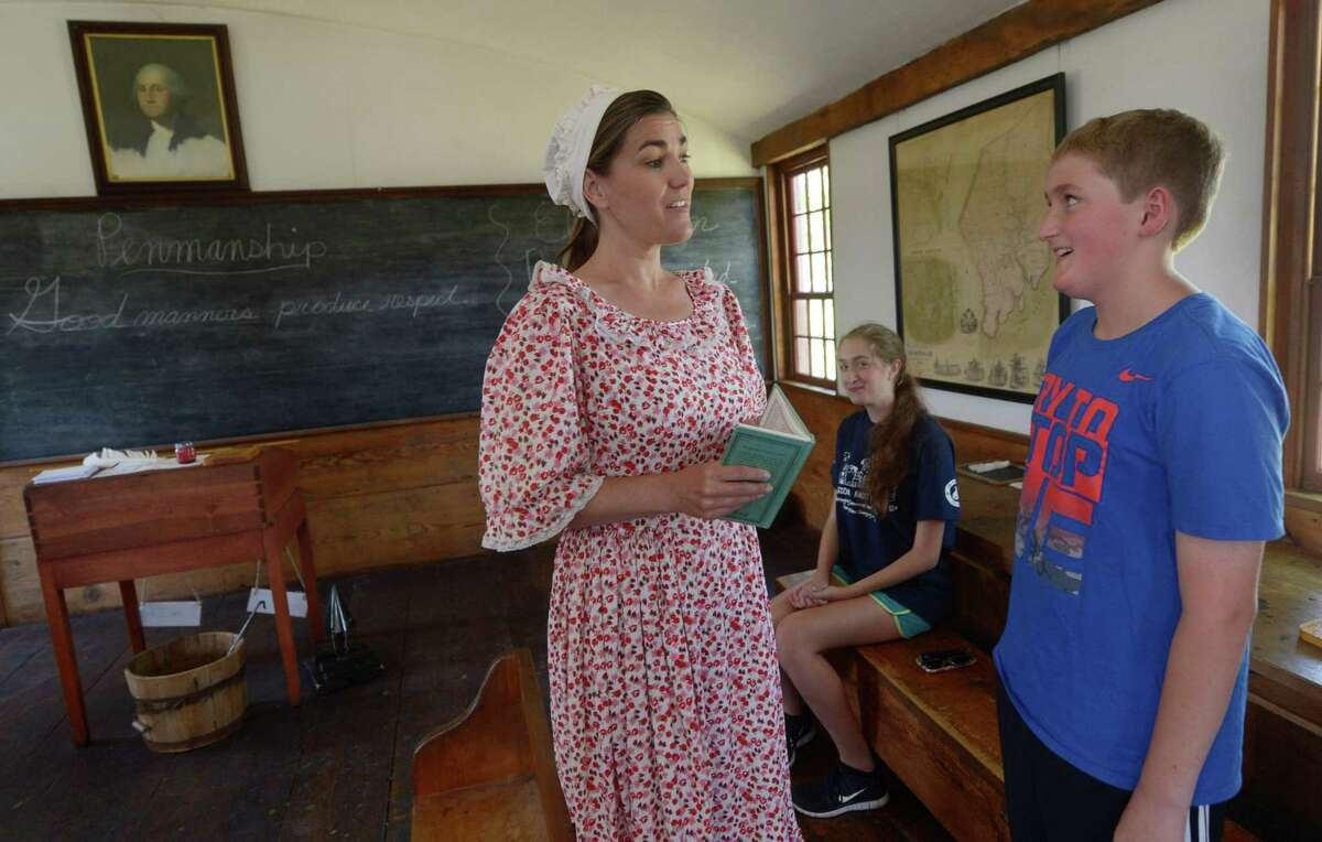 Shelly Howe portrays a colonial schoolmarm while visitors Victoria, center, and Nolan McCaffrey, get their lesson in the Little Red Schoolhouse .