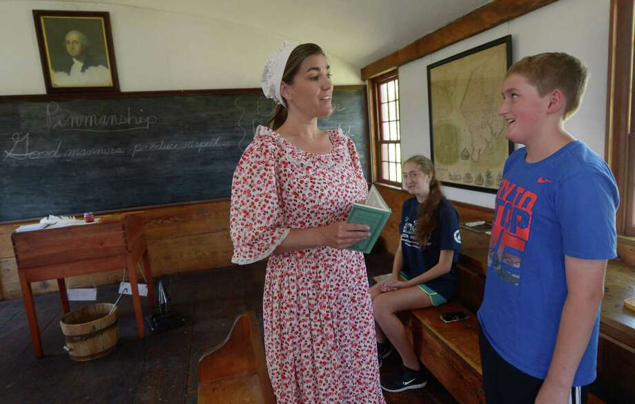 Shelly Howe portrays a colonial schoolmarm while visitors Victoria, center, and Nolan McCaffrey,  get their lesson in the Little Red Schoolhouse . Photo: Erik Trautmann / Hearst Connecticut Media / Norwalk Hour