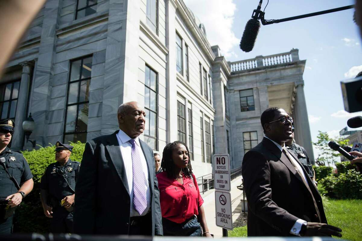 Bill Cosby, center left, listens to his spokesperson Andrew Wyatt, center right, as he speaks with members of the media as they depart from from Cosby's sexual assault trial at the the Montgomery County Courthouse in Norristown, Pa., Friday, June 9, 2017. (AP Photo/Matt Rourke)