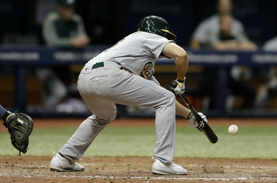 Oakland Athletics's Jaycob Brugman squeeze-bunts against Tampa Bay Rays relief pitcher Jose Alvarado during the sixth inning of the second game of a scheduled baseball doubleheader Saturday, June 10, 2017, in St. Petersburg, Fla. Athletics' Khris Davis scored. (AP Photo/Chris O'Meara) Photo: Chris O'Meara, Associated Press