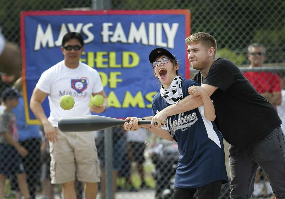 Kayla Janson, 17, gets assistance from her brother, Noah, in hitting the ball during a baseball game at the Miracle League of San Antonio on Saturday, June 10, 2017. The Miracle League of San Antonio - started by local attorney Mike Miller - gives special needs kids like Janson an opportunity to play the game of baseball in a supportive and fun environment. Six teams concluded their Spring season with each child getting a swing at bat with family and friends cheering them on. At the end, the children received trophies for their participation. (Kin Man Hui/San Antonio Express-News) Photo: Kin Man Hui, Staff / San Antonio Express-News / ©2017 San Antonio Express-News