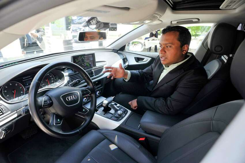 Audi engineer Kaushik Raghu sits inside an Audi A7 piloted driving prototype vehicle as he talks about the technology used in the car on Monday, May 23, 2016, in Albany, N.Y. Employees of the auto maker were outside the Capitol to talk with legislators about the driverless car. The State Senate is scheduled to vote on a bill that would advance self-driving technologies in New York State. (Paul Buckowski / Times Union)