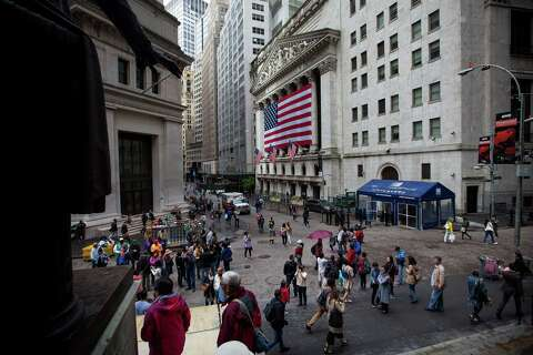 9e180c0c Pedestrians walk along Wall Street in front of the New York Stock Exchange  (NYSE)