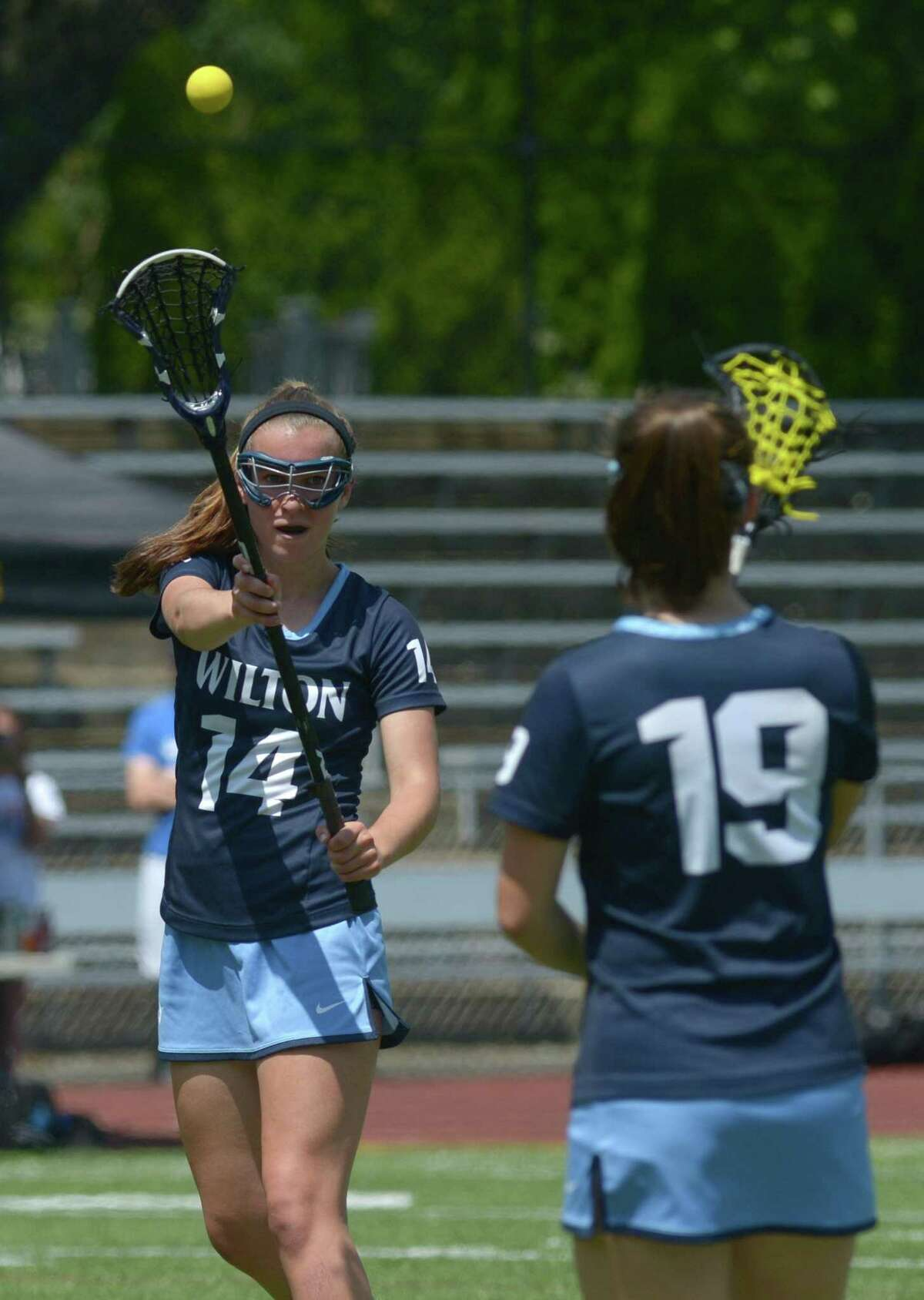 #14 of Wilton High School Carly Sullivan passes to #19 Sophie Sudaro Darien High School takes on Wilton in their Class L Girls Lacrosse championship Saturday, June, 10, 2017, at Jonathan Law High School in Milford, Conn.