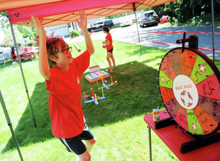 Jackson Jones, 10, of Greenwich, does jumping jacks after spinning the wheel. Photo: Tyler Sizemore / Hearst Connecticut Media / Greenwich Time