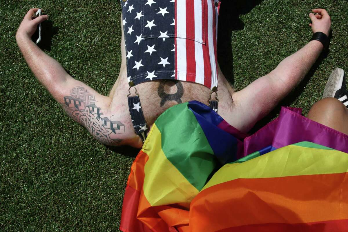Tank Hafertepen relaxes at Cal Anderson Park before the Seattle Pride March, Sunday, June 11, 2017. Several thousand marched through downtown in solidarity with the Pride March in Washington D.C. also taking place on Sunday.