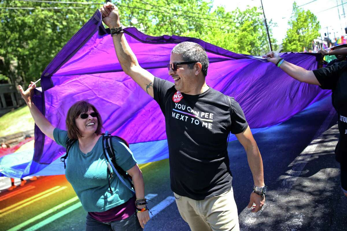 Vidette McDowell, left, and Rene De Los Santos hold up the corner of the giant Pride flag during the Seattle Pride March from Cal Anderson Park to Seattle Center, Sunday, June 11, 2017. Several thousand marched through downtown in solidarity with the Pride March in Washington D.C. also taking place on Sunday.