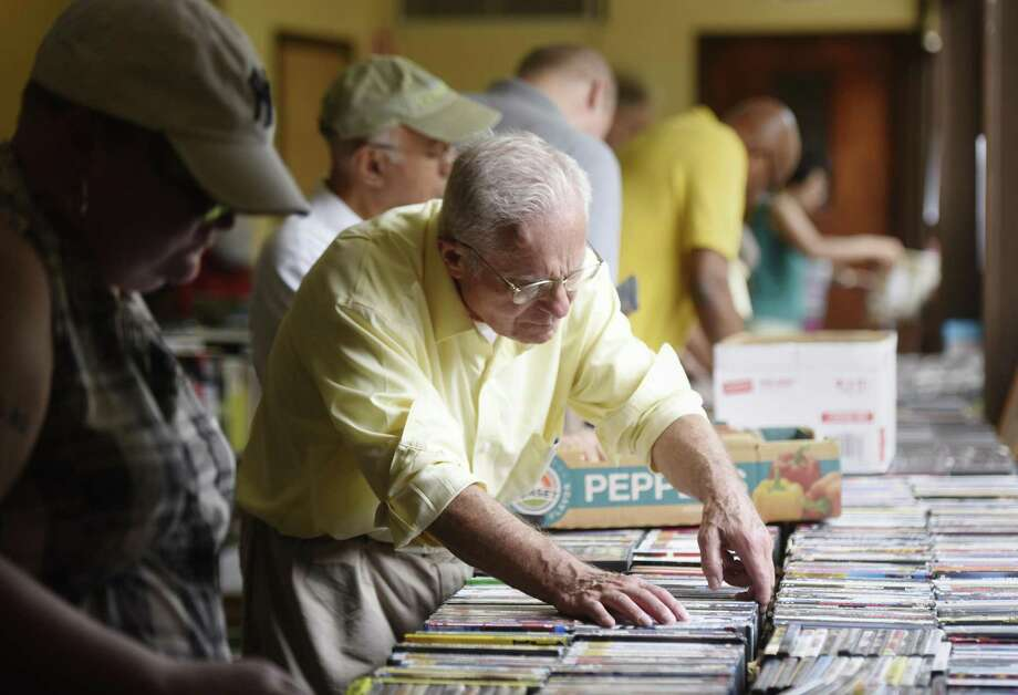 Robert Zipf, of Greenwich, browses 4-for-$1 DVD movies at the Friends of Byram Shubert Library Book Sale at St. Paul's Lutheran Church in the Byram section of Greenwich, Conn. Sunday, June 11, 2017. More than 200,000 books were available for purchase at the four-day event benefiting Friends of the Byram Shubert Library. Photo: Tyler Sizemore / Hearst Connecticut Media / Greenwich Time