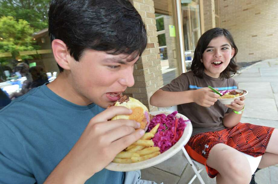 Wilton's Nathan Reznik takes a bite of a pulled beef brisket sandwich with brother Max during the Southern Connecticut Jewish Food Festival at Temple Israel in Westport on Sunday. The festival, sponsored by the Federation for Jewish Philanthropy of Upper fairfield County, included vendors and activities and a kosher food truck that were part of a day of learning about the Jewish table. Photo: Alex Von Kleydorff / Hearst Connecticut Media / Norwalk Hour
