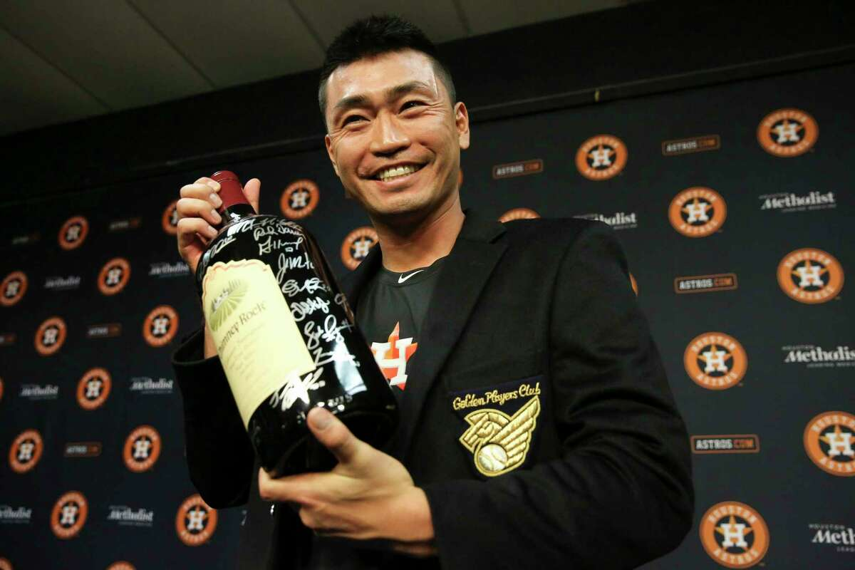 After singling in the sixth inning, left, for his 2,000th hit as a pro, outfielder Nori Aoki was presented with a bottle of wine signed by his Astros teammates and a black jacket signifying his entrance into Japan's Golden Players Club.