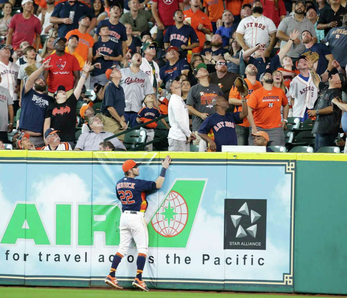 Astros right fielder Josh Reddick and the fans in his vicinity watch a three-run homer by Eric Young Jr. clear the fence in the fifth inning, putting the Angels up 9-6.
