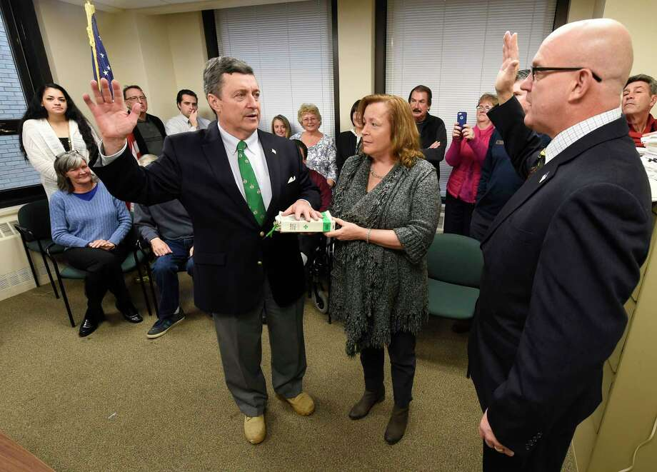 With his wife Katie Conners holding the bible, center, Albany County Comptroller Michael Conners, left,  is sworn in by Albany County Clerk Bruce Hidley for another four year term in office during a ceremony held Wednesday, Dec. 30, 2015, in the Albany County building in Albany, N.Y. (Skip Dickstein/Times Union) Photo: SKIP DICKSTEIN / 10034833A