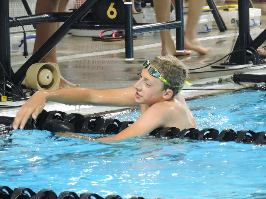 COM Aquatics' Collin Ruff talks to the swimmer in the next lane after competing in the boys 15-and-over 200-meter freestyle during Sunday's Frost Bank West Texas Invitational at FMH Natatorium.