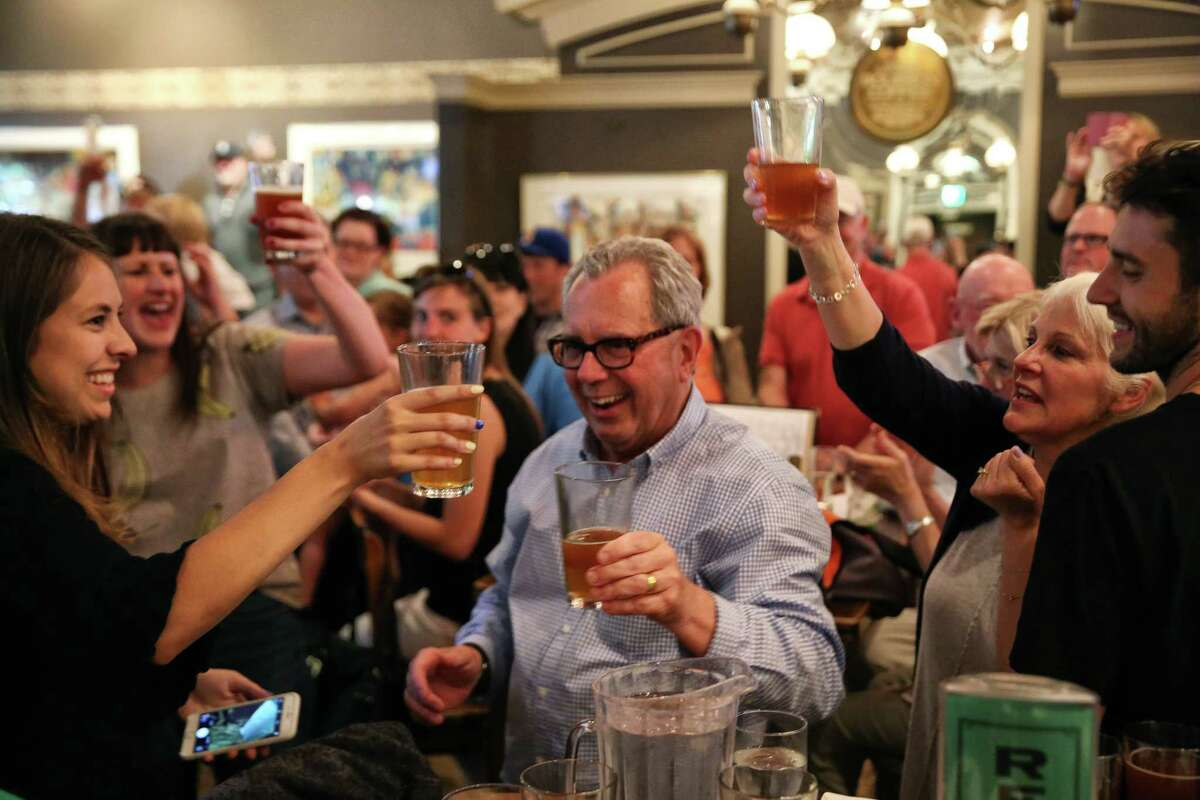 Friends and family raise a glass to bar co-founder Mick McHugh, center, as F.X. McRory's hosts an