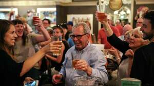 "Friends and family raise a glass to bar co-founder Mick McHugh, center, as F.X. McRory's hosts an ""Irish wake"" goodbye party on their last day in the historic Pioneer Square location where they opened 40 years ago, Sunday, June 11, 2017. The bar will be moving to a smaller location a few blocks away."