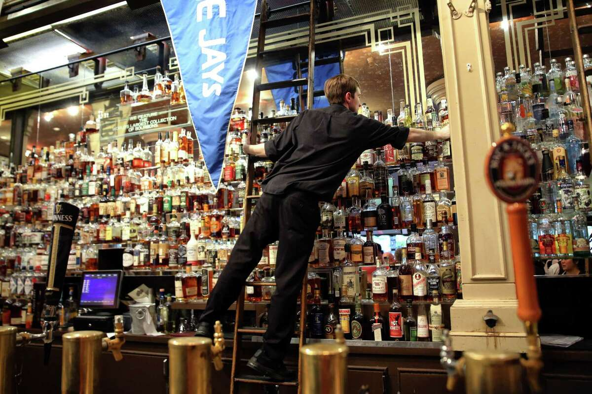 A bartender reaches for a whiskey bottle as F.X. McRory's hosts an