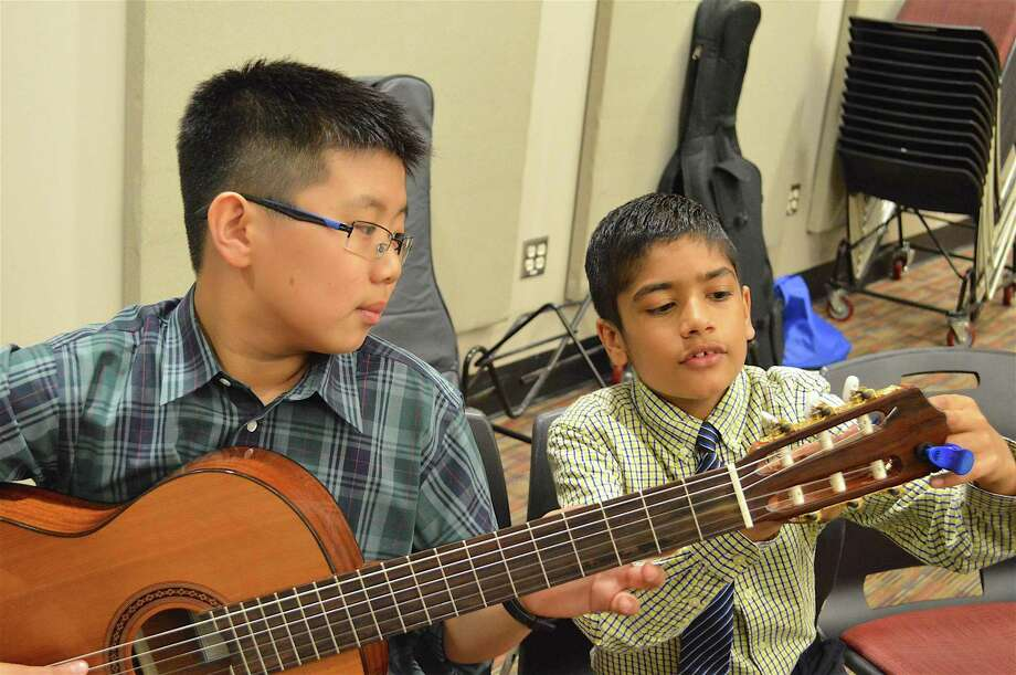 Arnav Chaudhary, 10, of New Cananaa, helps Andy Li, 11, of New Canaan, with his tuner at New Canaan Public Schools' Celebration of the Arts Gala Concert at New Canaan High School, Friday, June 9, 2017, in New Canaan, Conn. Photo: Jarret Liotta / For Hearst Connecticut Media / New Canaan News Freelance