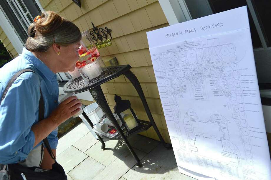 Ann Cathcart of Fairfield looks at the garden plans for a house on Evergreen Parkway during the Westport Historical Society's 26th annual Hidden Garden Tour, Sunday, June 11, 2017, in Westport, Conn. Photo: Jarret Liotta / For Hearst Connecticut Media / Westport News Freelance