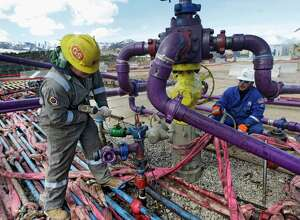 FILE - In this March 29, 2013 file photo, workers tend to a well head during a hydraulic fracturing operation outside Rifle, in western Colorado.