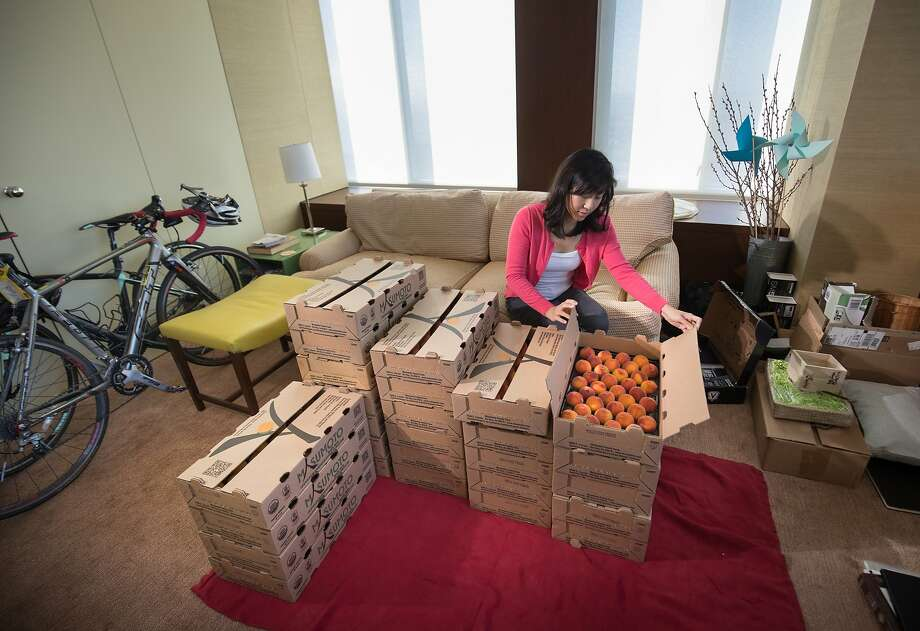 Pei-Ru Ko, director of Bay Area nonprofit Real Food Real Stories, in her S.F. apartment with Gold Dust peaches picked up the day before from Masumoto Family Farm. Photo: Paul Kuroda, Special To The Chronicle