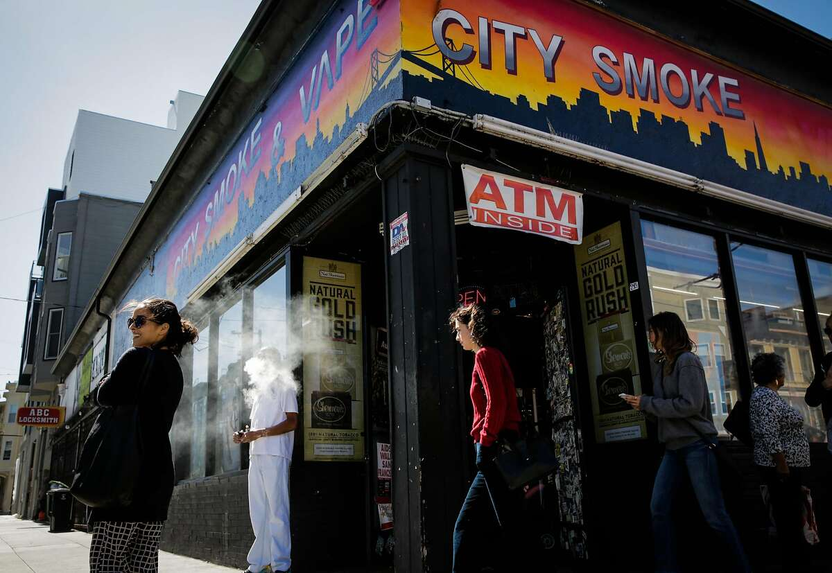 Store employee Khalil G. (second from left) takes a smoke break outside of City Smoke and Vape Shop in San Francisco, California, on Sunday June 11, 2017.