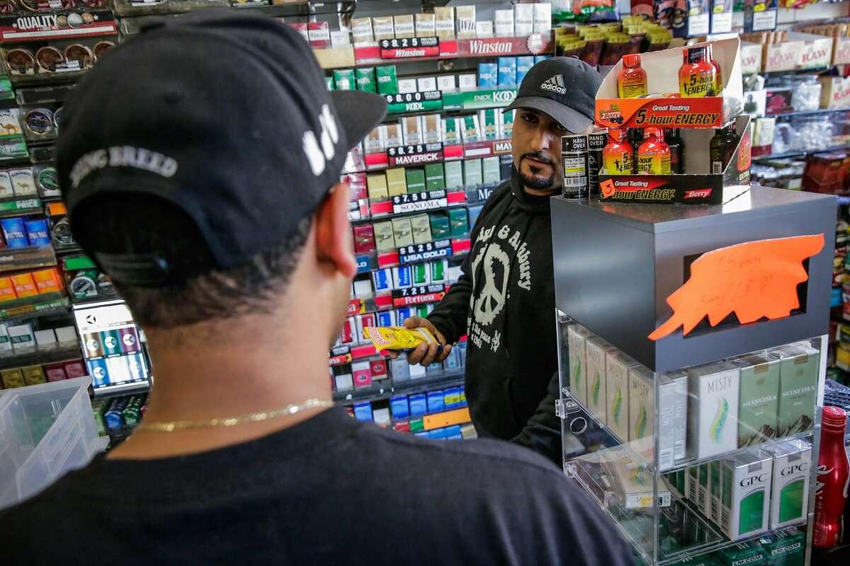 Store employee Majid Abbas (right) helps customer Alexander Maldonado buy flavored tobacco at City Smoke and Vape Shop in San Francisco, California, on Sunday June 11, 2017.