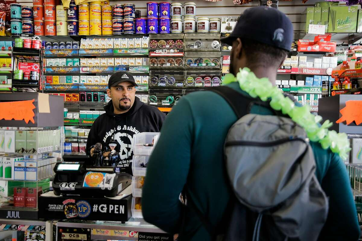 Employee Majid Abbas (left) helps a customer buy flavored tobacco at City Smoke and Vape Shop in San Francisco in 2017.