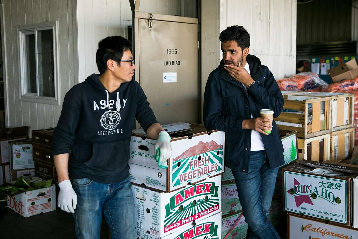 CEO and co-founder of MoveButter, Chai Mishra, talks to an employer at Lao Biao, Sean Liang, about the prices of taiwanese cabbage in South San Francisco, Calif. Monday, June 12, 2017.