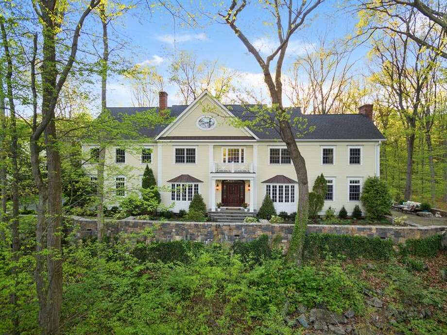 The buttercream-colored colonial house at 43 Stony Brook Road sits in a tranquil, private setting yet walking distance to the Metro North train station and high school, close to shops and restaurants.