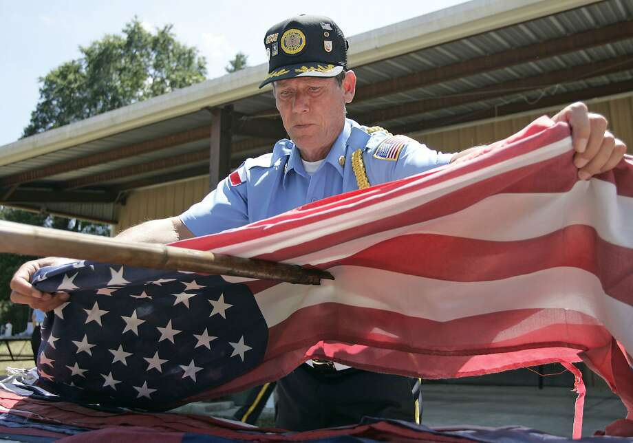 American Legion member Leon Fritsche places an American flag on the end of another member's stick during the group's flag retirement ceremony for Flag Day on Sunday at the American Legion Hall Post 618 in Willis, Texas. Photo: Eric S. Swist, Staff Photo By Eric S. Swist