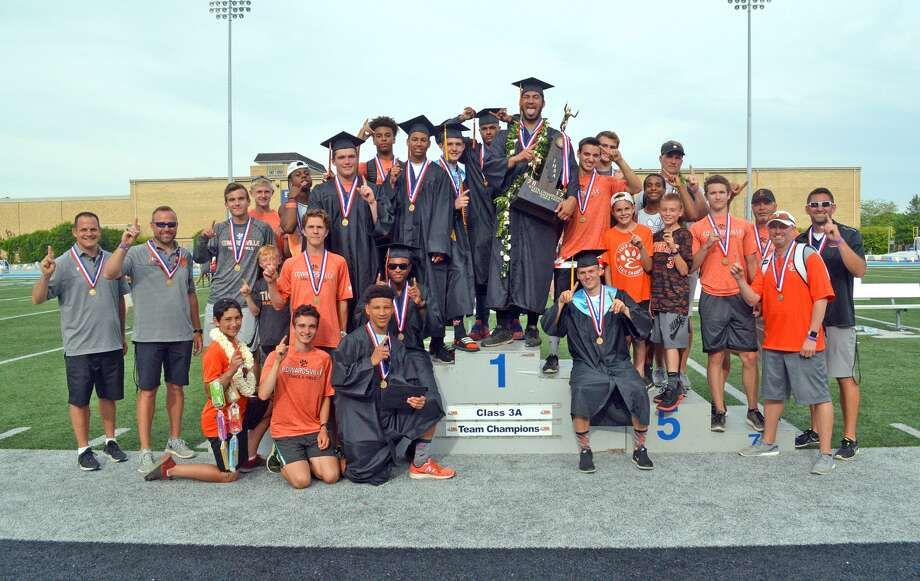 Edwardsville boys' track and field team poses with the Class 3A state championship trophy after winning the title at Eastern Illinois University.